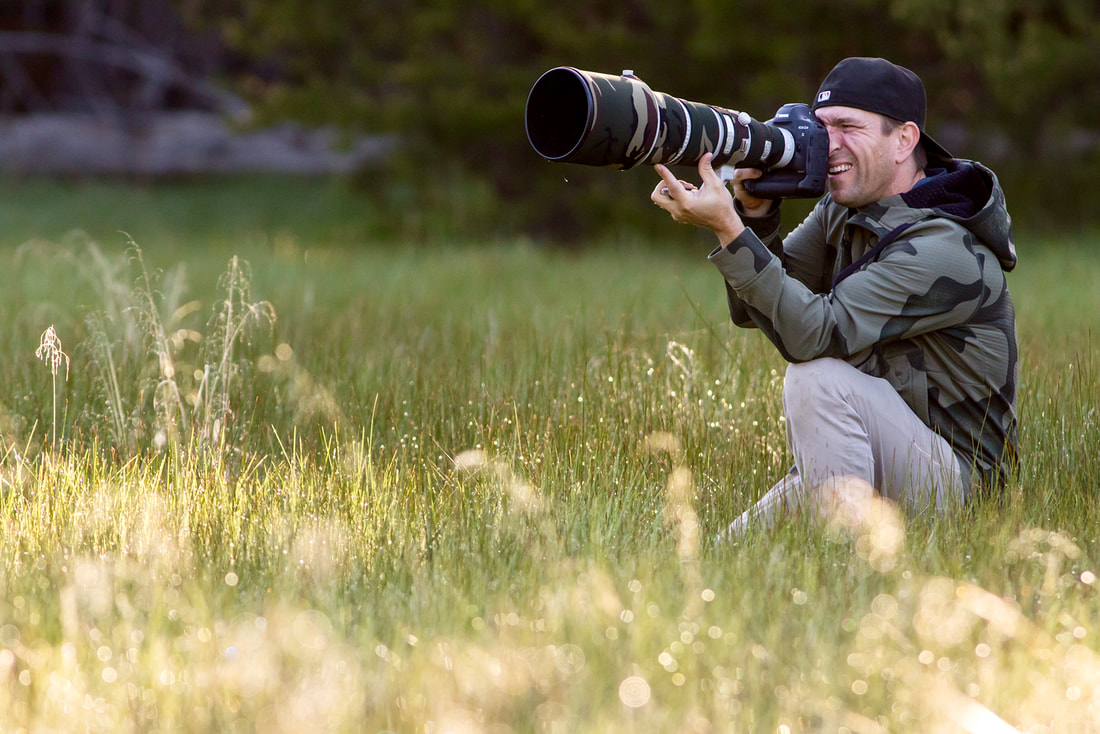 Nature Photographer John Fox on a shoot in tall grass with a telephoto lens.